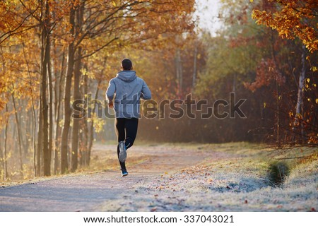 Young man running at park during autumn morning
