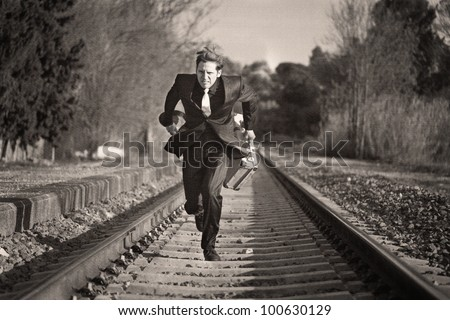 Young man running down the railway tracks with luggage and suit - stock photo