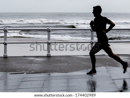 Young man running down the street - stock photo