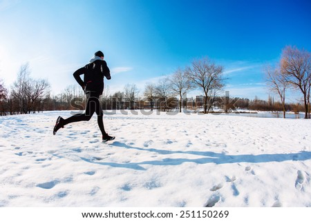 Young man running during winter at park - stock photo