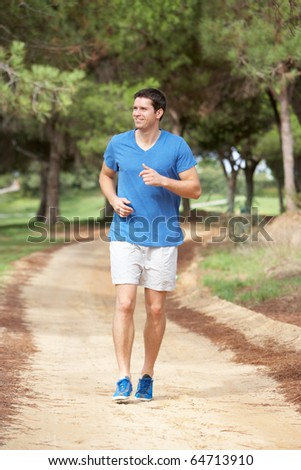 Young man running in park - stock photo