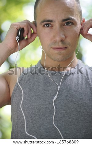 Young man running in the woods listening music