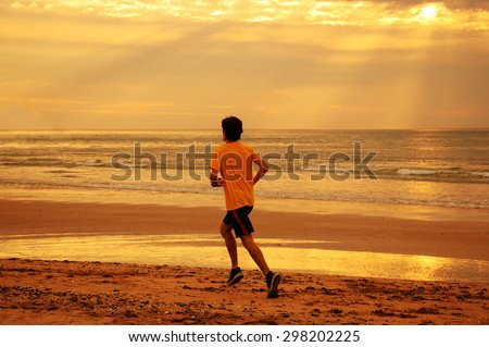 Young man running on beach at sunset. Back view. Dramatic sky lighting with sun rays glowing through the clouds. A game of light and shadow. Toned photo. - stock photo