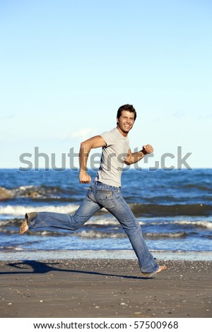 Young man running on beach barefoot in casual clothing - stock photo