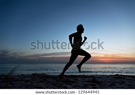 Young man running on the beach at the sunset - stock photo