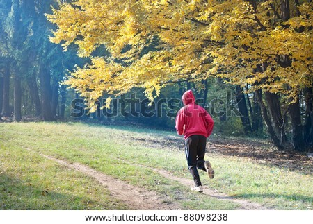 young man running  the autumn forest - stock photo