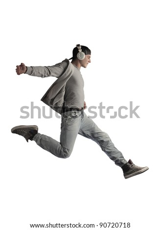 Young man running while listening to music - stock photo
