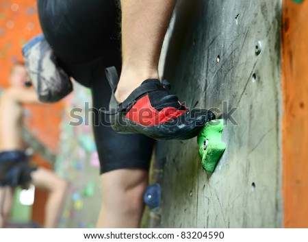 Young man's foot climbing indoor wall - stock photo
