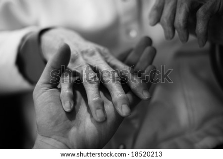 Young man 's hand holding senior's hand - stock photo