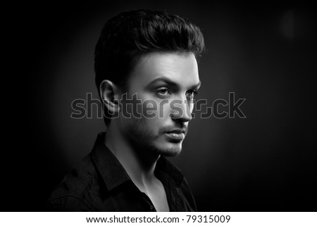 Young man's portrait. Close-up face against black background - stock photo