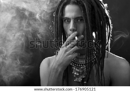Young man's portrait. Stylish handsome guy with dreadlocks and a cigarette and a variety of stylish silver jewelry dreadlocks and  - Close-up face  - stock photo