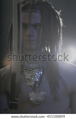 Young man's portrait. Stylish handsome sexy Guy with Dreadlocks and ethnic Jewelry, Accessories (necklace, bracelet) Close-up face. Tribal Style. Trendy youthful man's look with katana sword - stock photo