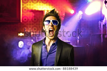 Young man screaming in a disco - stock photo