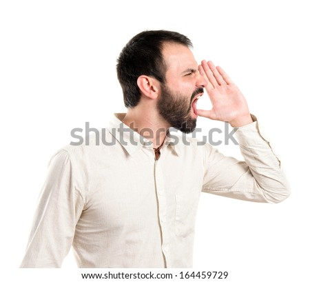 Young man screaming over white background