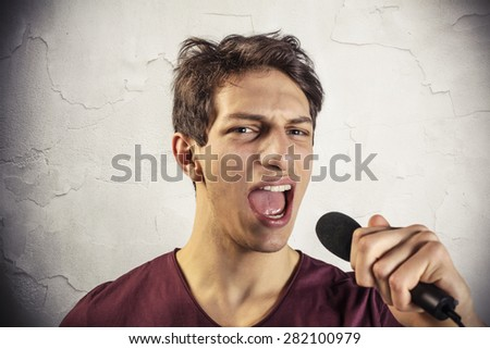 Young man screams into a microphone - stock photo