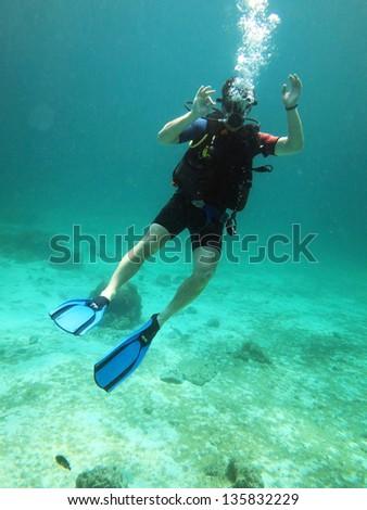 Young Man Scuba Diver between Water Surface - stock photo