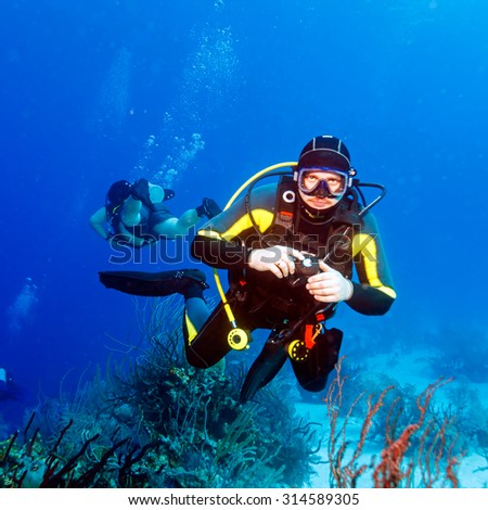 Young Man Scuba Diver between Water Surface and Sea Bottom - stock photo