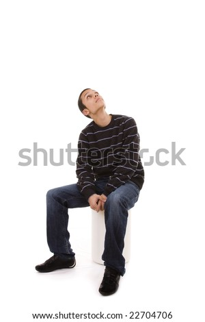young man seated in a bench looking up to the copy space - stock photo