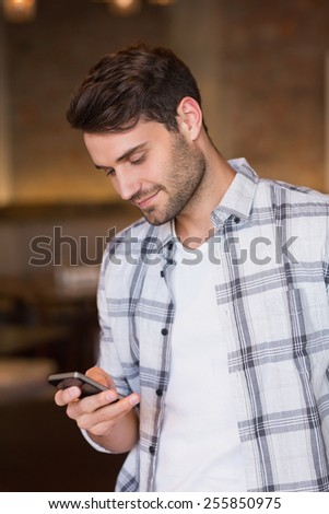Young man sending a text at the cafe