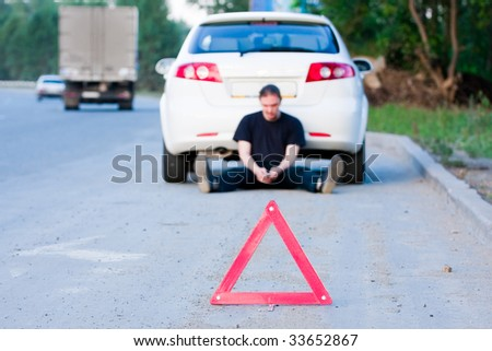 Young man sends an sms sitting by a white car. Focus is on the red triangle sign - stock photo