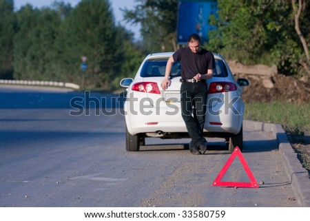Young man sends an sms standing by a white car - stock photo
