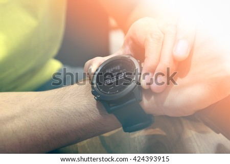 Young Man setting watch on his wrist