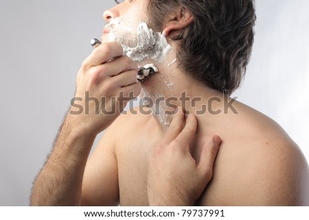 Young man shaving - stock photo