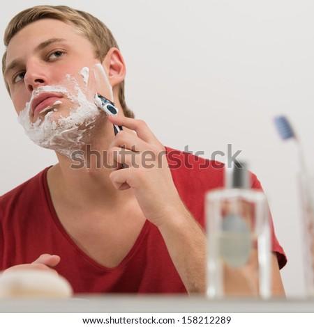 Young man shaving at home - stock photo