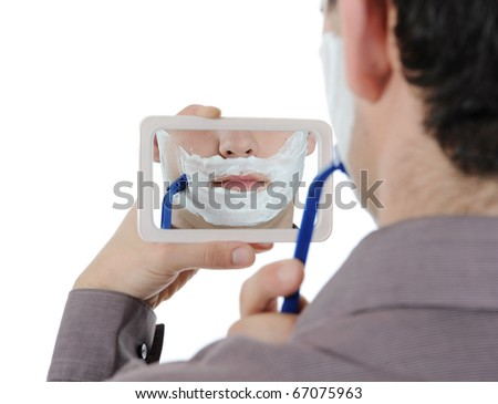 Young man shaving at the mirror. Isolated on white background