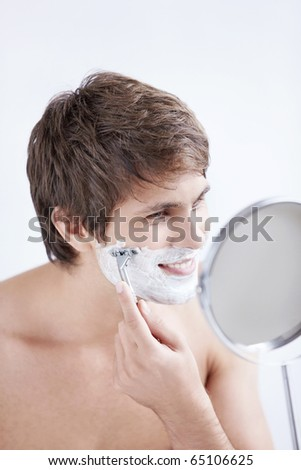 Young man shaving at the mirror on a white background - stock photo