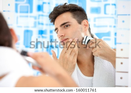 Young man shaving by electric shaver - stock photo