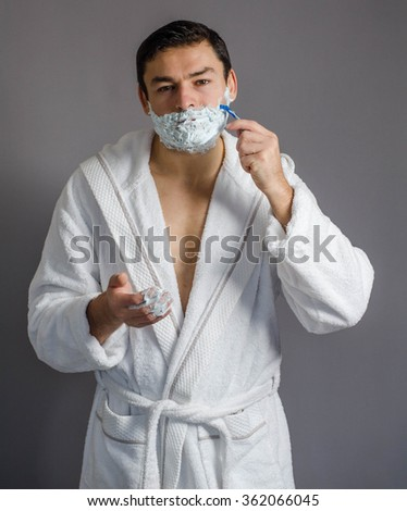 young man shaving his beard with - stock photo