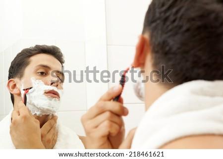 Young man shaving his beard with razor at the bathroom - stock photo