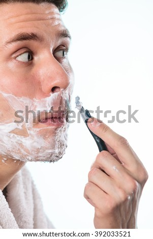 Young man shaving using razor with cream foam. Handsome guy removing face mustache hair. Skin care and hygiene. - stock photo
