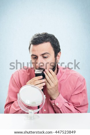 Young man shaving with electric razor - stock photo