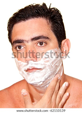 Young man shaving with his face covered in foam  on a white background