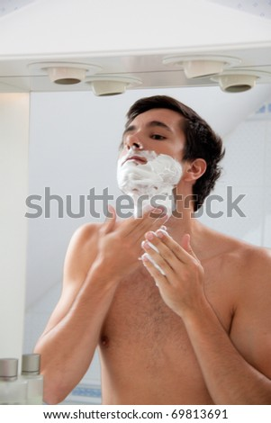 Young man shaving with razor and shaving cream in bathroom - stock photo