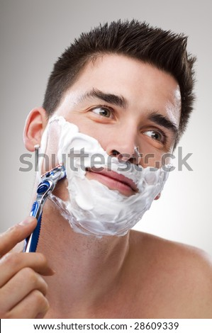 young Man shaving with razor close up