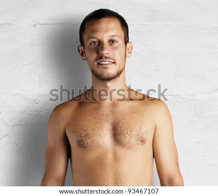 young man shirtless against a white wall - stock photo