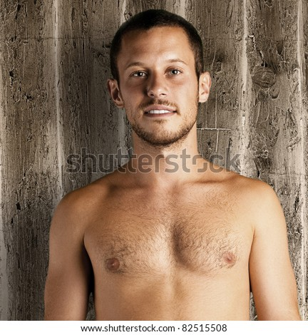 young man shirtless on a wooden background - stock photo