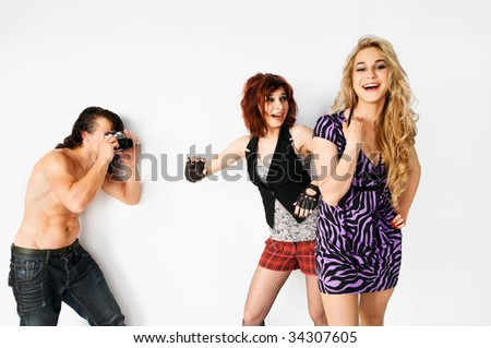 Young man shooting two beautiful girls at the studio - stock photo