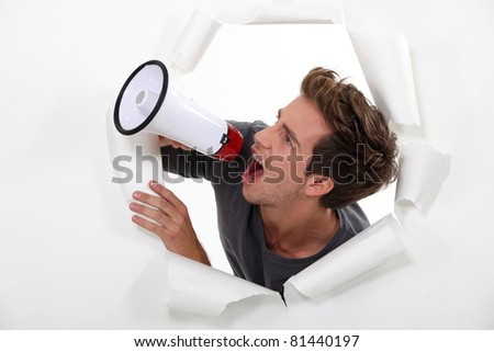Young man shouting into a megaphone - stock photo