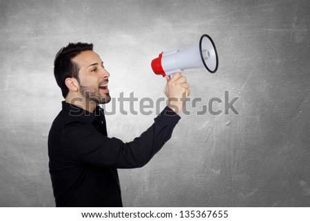 Young Man Shouting Through Megaphone Over Gray Background - stock photo