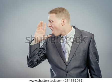 Young man shouting with hands cupped to his mouth - stock photo