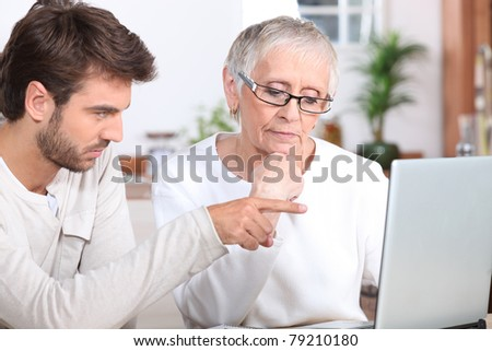 Young man showing a senior woman how to use a laptop - stock photo