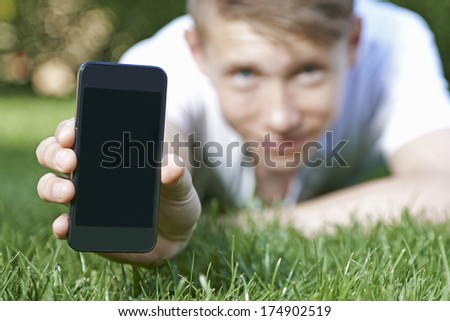 Young man showing a smartphone to the camera - stock photo