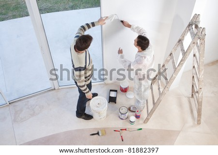 Young man showing a spot on the wall to painter - stock photo