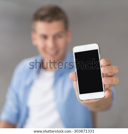 Young Man Showing an Empty Black Screen of his Mobile Phone at the Camera in Close up, Emphasizing Copy Space. - stock photo