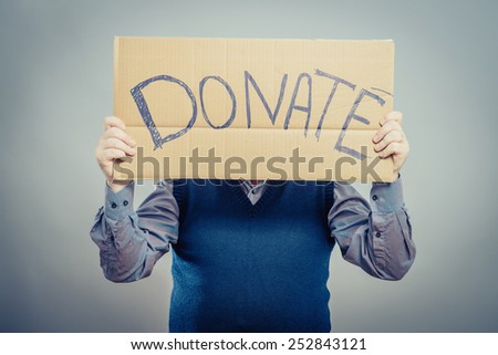young man showing board with text: Donate - stock photo