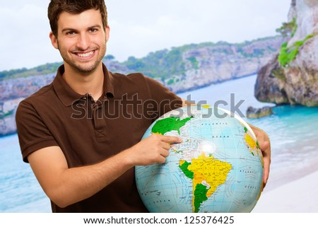Young Man Showing Destination On Globe, Outdoors - stock photo